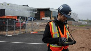 worker at construction site in vest with mobile tablet