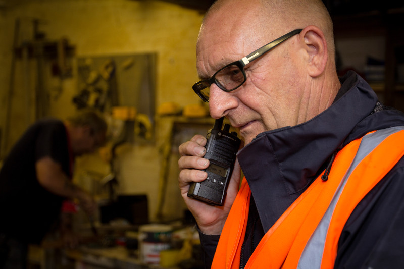worker in vest on Motorola Two-Way Radios