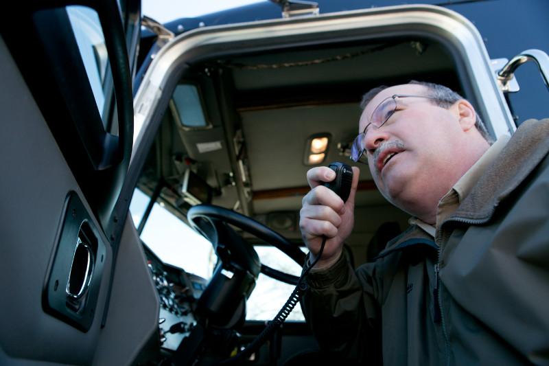 man using Motorola CB radio in truck