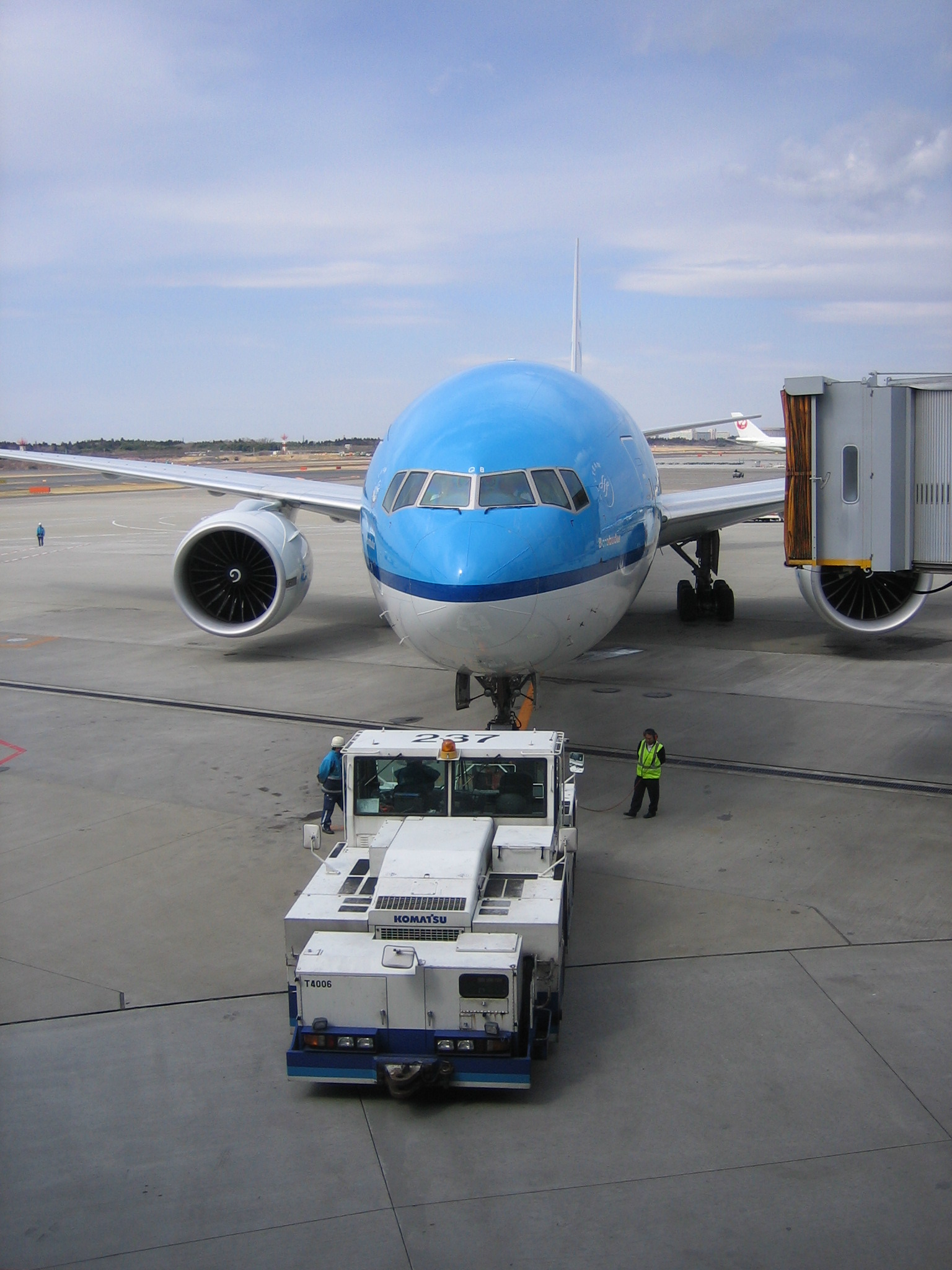 KLM 777 at gate with ramp worker on two way radio