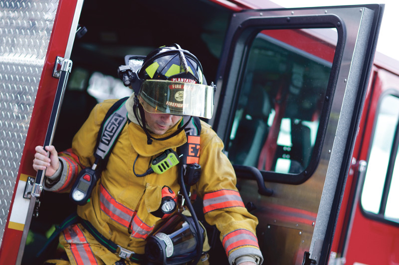 firefighter with PPE and two-way radio steps off truck