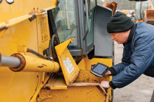 heavy equipment operator holds handheld device