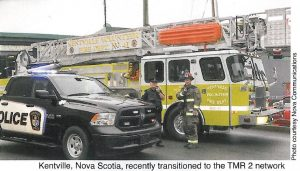 police officer and fire fighter talk on 2-way radio at emergency scene