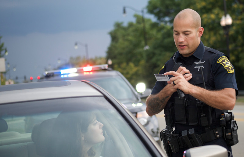 police officer uses two-way radio to relay information about driver