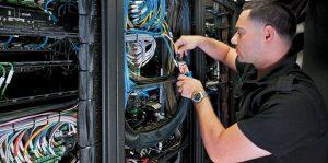 tech guy checks wires on rack server