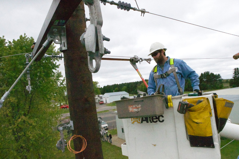 public safety worker approaches power line in bucket on radio